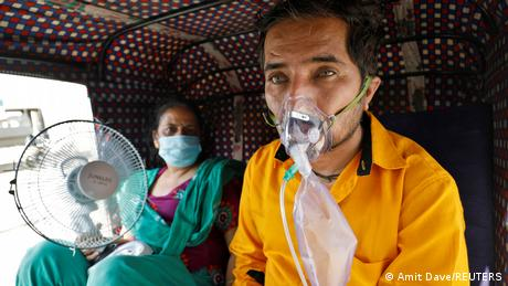 A patient wearing an oxygen mask looks on as his wife holds a battery-operated fan while waiting inside an auto-rickshaw to enter a COVID-19 hospital for treatment