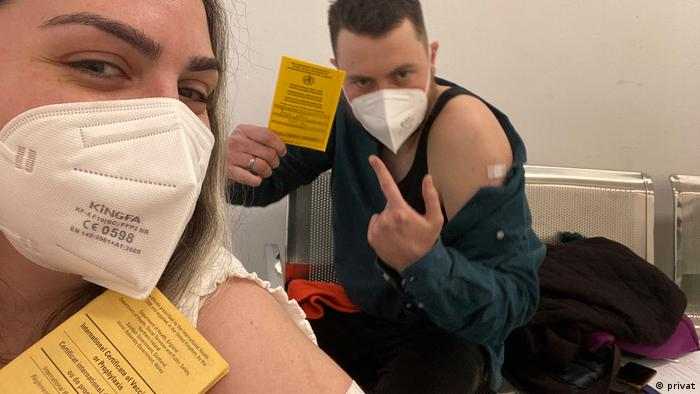 The author and a friend pose with their vaccination certificate.