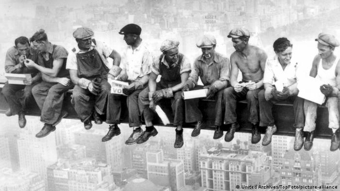 Black and white photo of Empire State Building construction workers sitting at dizzying heights on a T-bar and having breakfast break.
