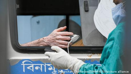 A health worker tests blood oxygent level of a patient inside an ambulance who tested positive for COVID-19 at a hospital in Kolkata, India