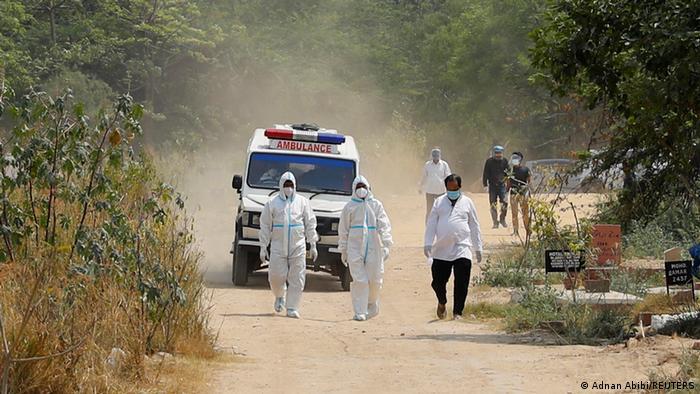 Foto simbólica de personal de Salud con equipo de seguridad frente a una ambulancia en India.