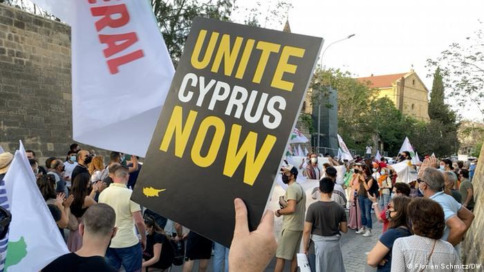 Demonstration, im Vordergrund ein Plakat mit der Aufschrift Zypern jetzt vereinigen