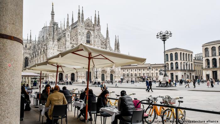 Gäste sitzen an den Tischen im Außenbereich eines Restaurants am Mailänder Dom