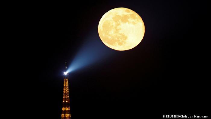 Pun mesec sija iznad Pariza. Osvetljava ga čak i refllektor sa vrha Ajfelove kule.