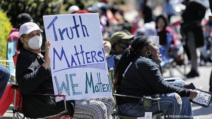 Pessoas cantam no centro de Elizabeth City, N.C. no dia 26 de abril de 2021, enquanto manifestantes e mídia se reúnem antes de uma coletiva de imprensa com a família de Andrew Brown Jr., baleado e morto na semana anterior.