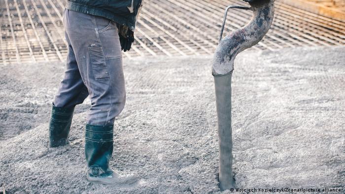 Ein Arbeiter gießt eine Betondecke auf einer Baustelle.