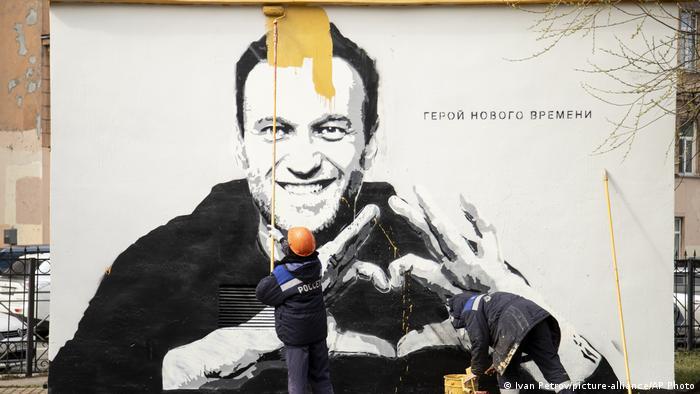 Сотрудник ЖКХ закрашивает граффити с портретом оппозиционного политика Алексея Навального в Санкт-Петербурге