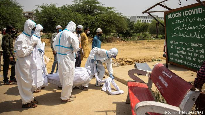 Indian health workers carry a body in a white cowl