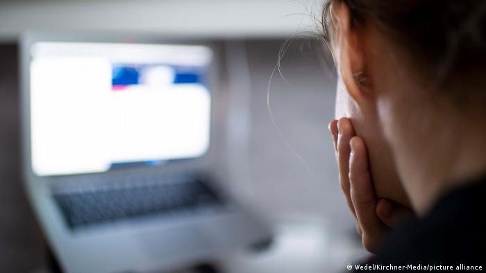 Der Kopf einer jungen Frau ist von hinten zu sehen. Sie sitzt vor einem Laptop, der im Hintergrund unscharf zu sehen ist.