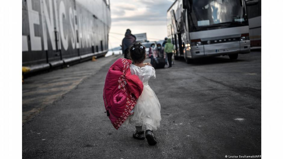 Little girl seen from back walking to a bus at a port. Photo: Louisa Gouliamaki, Lesbos, Greece