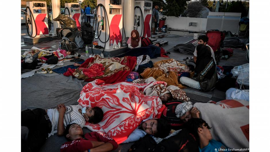 People sleeping on ground at gas station. Photo:| Louisa Gouliamaki, Lesbos, Greece