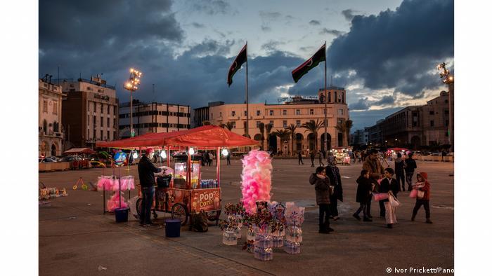 Praça na Líbia tem adultos e crianças em frente a um carrinho que vende algodão-doce e pipoca