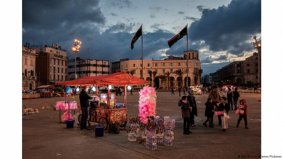 Candy stall lit up at twilight in the middle of a square. Photo: Ivor Prickett, Libya