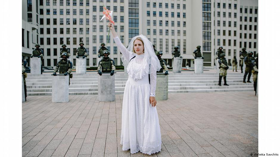 Woman in wedding dress standing in front of security forces with shields. Photo: Violetta Savchits, Belarus