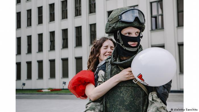 Manifestante vestindo um vestido vermelho abraça um policial uniformizado nas ruas de Belarus