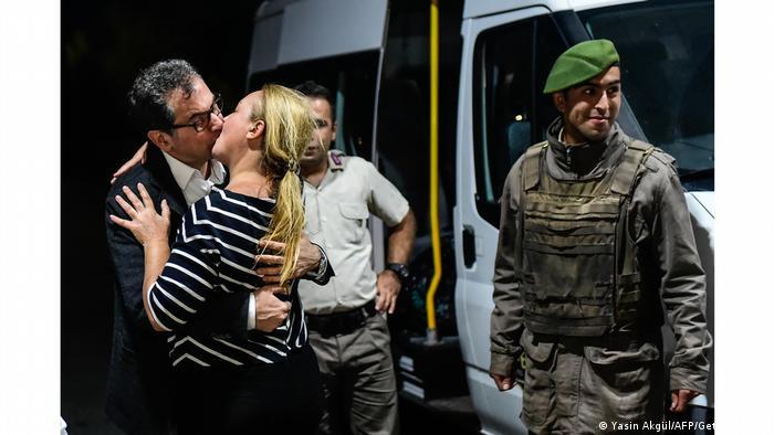 Jornalista recém-libertado da prisão, Kadri Gürsel beija sua esposa ao lado de dois guardas e uma van, na Turquia
