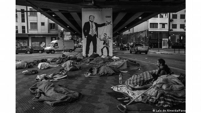Moradores de rua dormem em seus cobertores debaixo de uma ponte em São Paulo