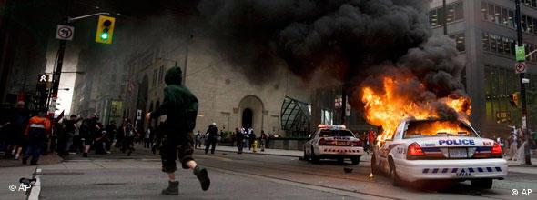 An activist runs past a burning police car in Toronto's financial district during the G20 Summit Saturday, June 26, 2010. (AP Photo/The Canadian Press, Darren Calabrese