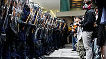 A protester with gas mask and camera participates in a stand off with a line of riot police