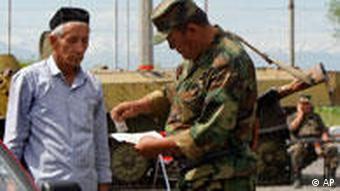 A Kyrgyz soldier checks driver's documents at a check point in the southern city of Osh, Kyrgyzstan