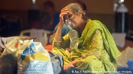 An Indian woman inside a temporary COVID-19 center with breathing mask