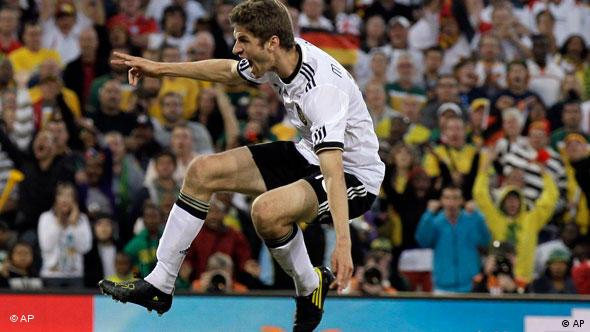 Germany's Thomas Mueller, top, scores his side's fourth goal past England goalkeeper David James