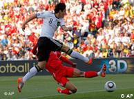 Germany's Mesut Oezil, front, fires a shot