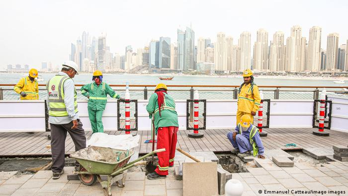 Migrant workers finishing the pavement on Bluewaters Island