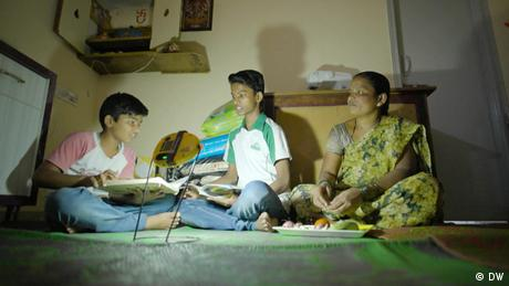 A family with a small light sit on the floor of a home in a slum in India, with textbooks and a plate of food