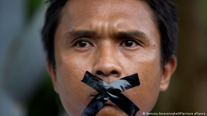 A Myanmar journalist with his mouth sealed with tape, symbolizing the government's recent crackdown on media
