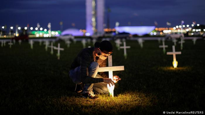 A man lights a candle next to a cross symbolising the ones who died from the coronavirus disease.