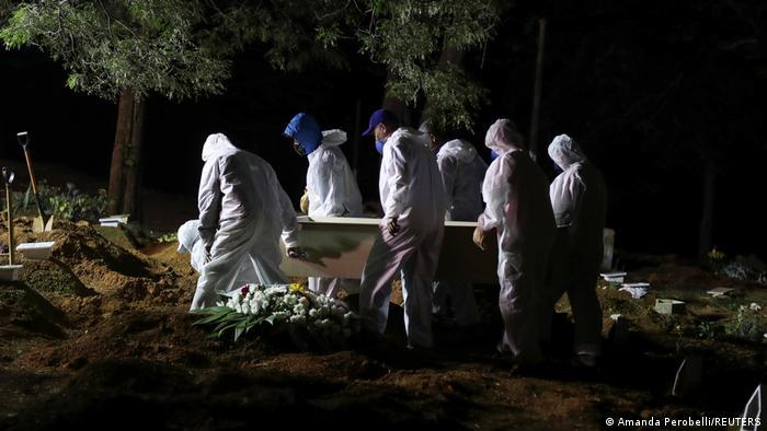 Coveiros enterram uma vítima da covid-19 em São Paulo