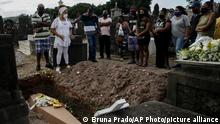 Relatives attend the burial service of Mariana de Jesus, 77, who died from complications related to COVID-19, at the Inahuma cemetery in Rio de Janeiro, Brazil, Wednesday, April 28, 2021. (AP Photo/Bruna Prado)