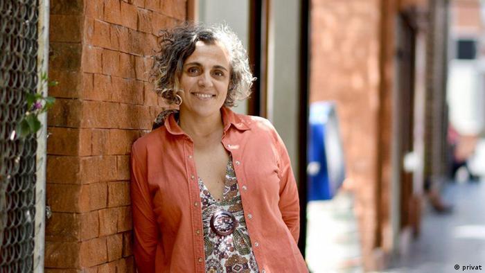 Die Journalistin Silvia Trujillo lehnt an einer roten Backsteinwand und lächelt
