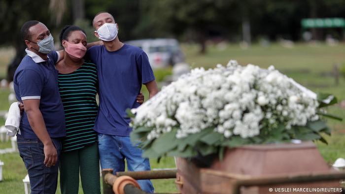 A média móvel de mortes em 7 dias no Brasil está acima de 2 mil há 49 dias. Mãe e dois filhos lamentam morte do pai, em frente ao caixão em cemitério de Brasília