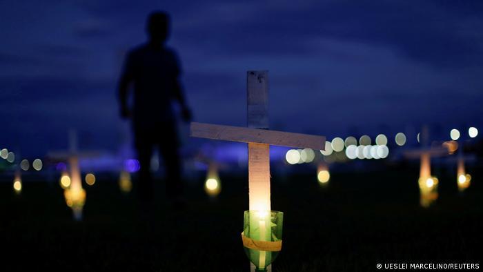 Cruzes iluminadas com velas em homenagem aos mortos pela covid-19 em frente ao Congresso Nacional. Taxa de mortalidade por grupo de 100 mil habitantes no Brasil subiu para 198,4