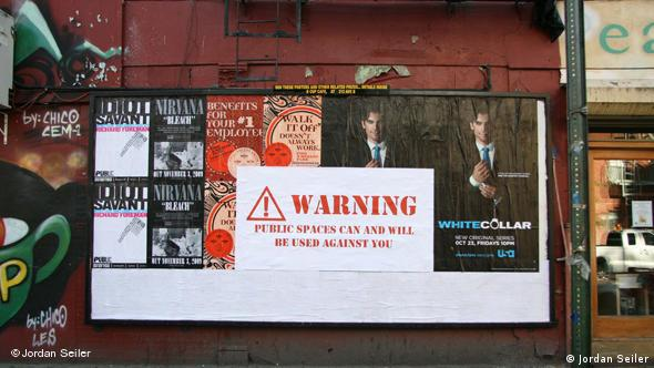 A poster reading Warning: Public spaces can and will be used against you, covering a commercial billboard