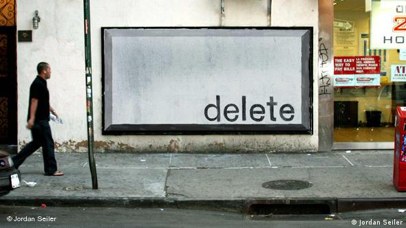 A billboard in New York City painted over white, with the word delete