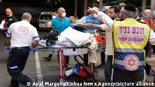 Ein bei der Massenpanik auf dem Lag Ba'Omer verletzter Mensch wird von Sanitätern auf einer Trage fortgebracht
