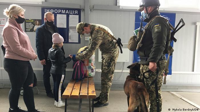 Українські службовці проводять огляд речей тих, хто перетинає лінію розмежування