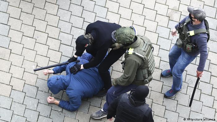 Белорусские милиционеры задерживают участника акции протеста в Минске, ноябрь 2020 года