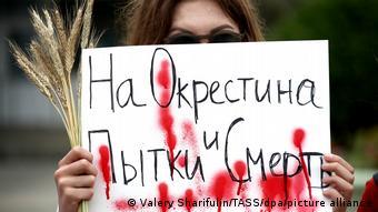 Участница акции протеста в Минске с плакатом На Окрестина пытки и смерть
