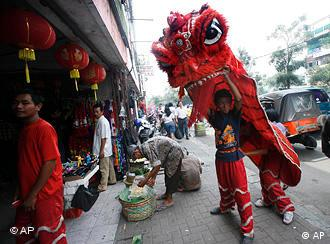 Lion dancers perform for small money at the China Town in Jakarta, Indonesia, Wednesday, Feb. 3, 2010. Ethnic Chinese communities in the world's most populous Muslim country are preparing to celebrate the start of the Lunar Year of the Tiger. (AP Photo/Tatan Syuflana)