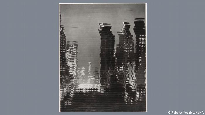 Ein verschwommenes Foto in Schwarz-weiß zeigt eine Stadtsilhouette.