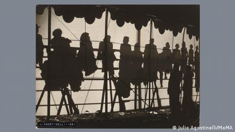 'Circus' by Julio Agostinelli (1951): Black-and-white photo showing different silhouettes of people sitting in the stands of a circus.