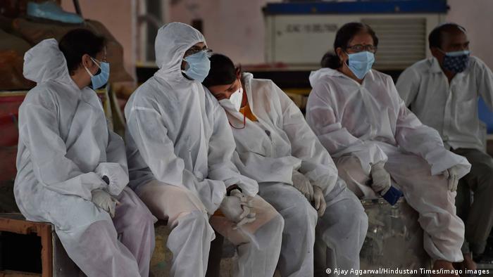Familiares de pacientes con COVID-19 esperan en un hospital de Nueva Delhi, en India.
