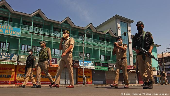 Indien: Mit Gewehren bewaffnete Polizisten mit Mundschutzen patrouillieren auf einer Straße während der Corona-Pandemie