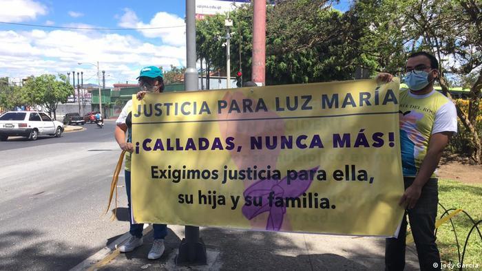 Eine Frau und ein Mann mit Mund-Nase-Schutz halten ein gelbes Plakat, auf dem sie Gerechtigkeit für die ermordete Staatsanwältin Luz Maria fordern