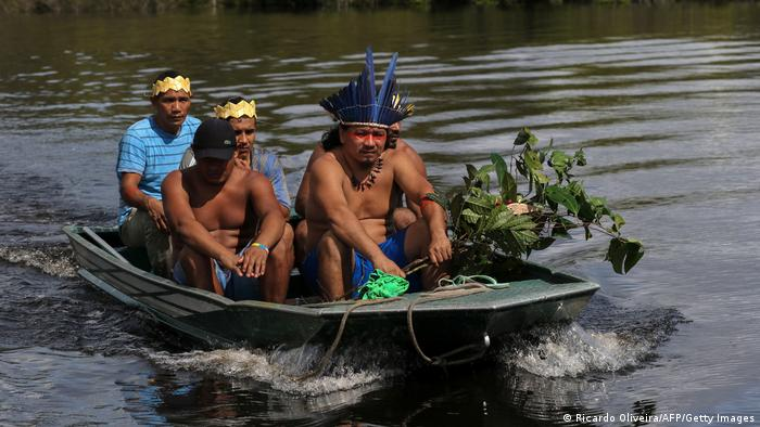 A group of indigenous men in a boat on the Amazon River