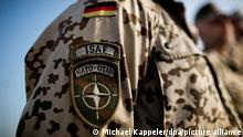 ARCHIV FOTO - 03.10.2013 *** - Ein Bundeswehrsoldat mit dem Abzeichen der Nato Mission ISAF steht am 03.10.2013 in Kundus in Afghanistan bei einem Appell. Foto: Michael Kappeler/dpa (zu dpa «Kabinett beschließt Mandate für Mali und Afghanistan» vom 04.02.2014) +++ dpa-Bildfunk +++